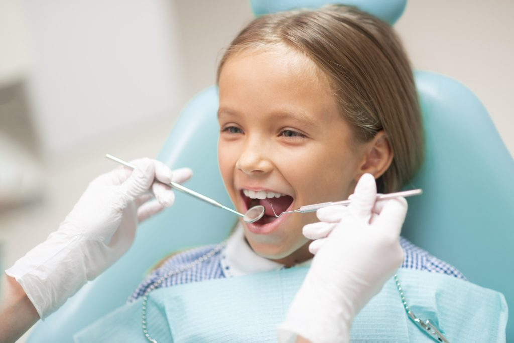 Young Girl in Dentist Chair getting Dental Checkup