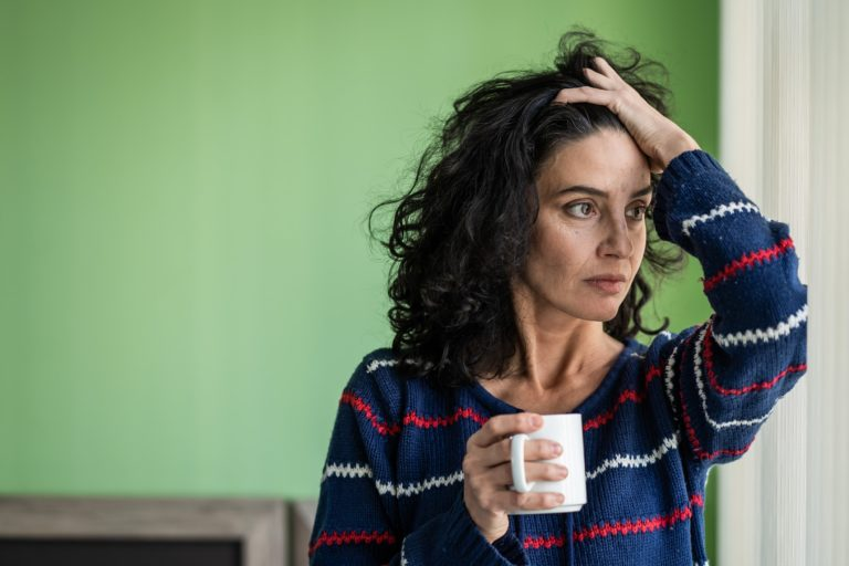 A woman looking stressed and holding a coffee mug