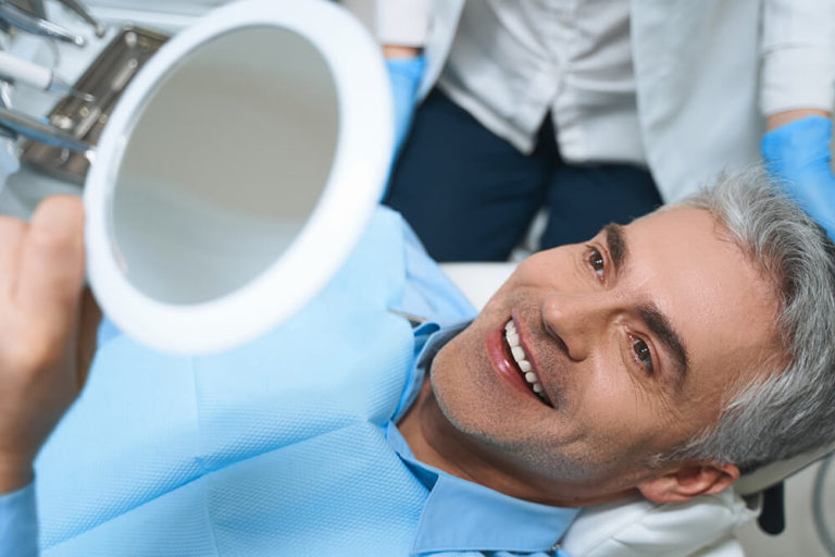 A male dental patient laying back in a dental chair while holding a mirror above his head and smiling as he checks his teeth