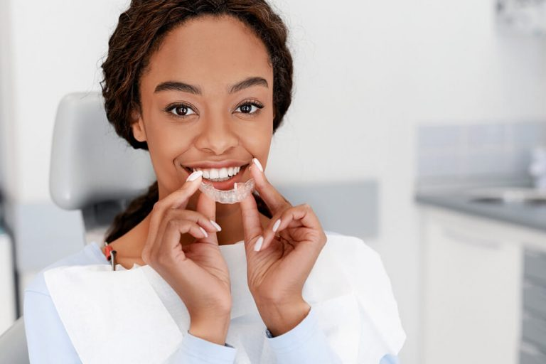 An African American woman sits in a dental chair and holds an Invisalign tray to her mouth